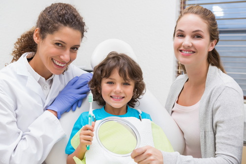 Pediatric dentist showing little boy how to brush teeth with his mother at the dental clinic